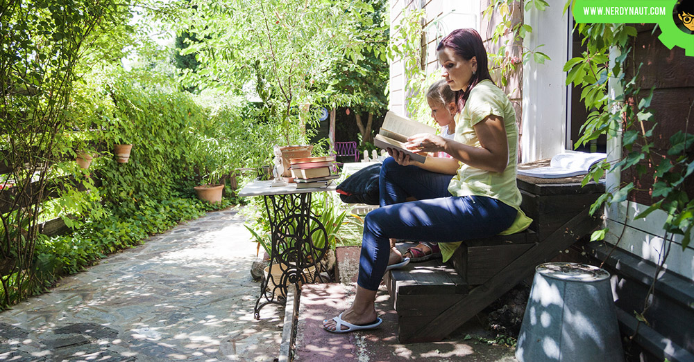 Mom and daughter reading books in an organized backyard